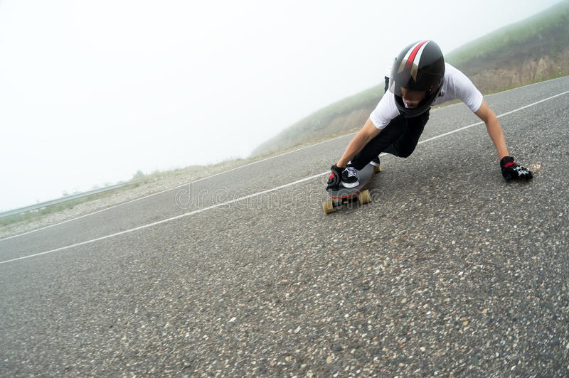 A young guy in a full face helmet in a slide passes a turn. A young guy in a full face helmet on a country road in a slide passes a turn against a background of royalty free stock photo