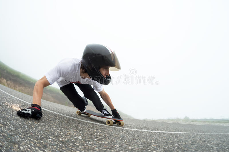 A young guy in a full face helmet in a slide passes a turn. A young guy in a full face helmet on a country road in a slide passes a turn against a background of royalty free stock image