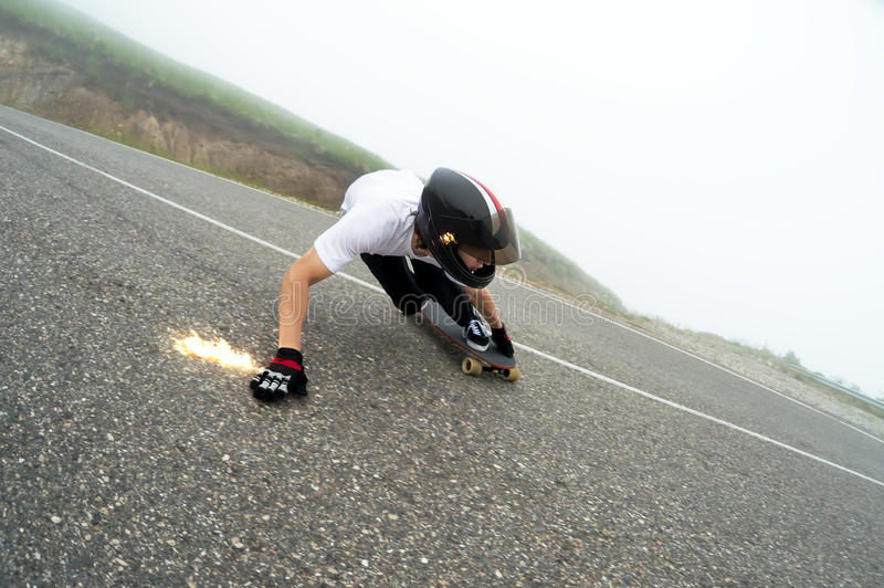A young guy in a full face helmet in a slide passes a turn. A young guy in a full face helmet on a country road in a slide passes a turn against a background of stock photography