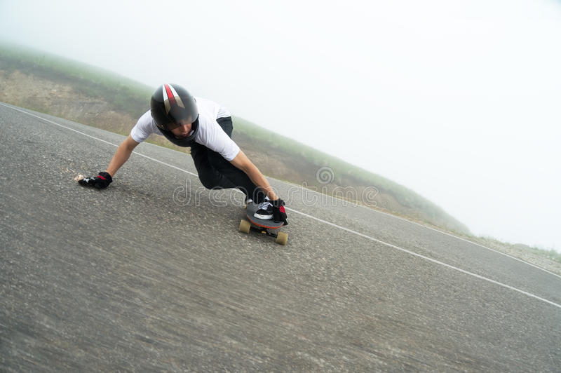 A young guy in a full face helmet in a slide passes a turn. A young guy in a full face helmet on a country road in a slide passes a turn against a background of royalty free stock images
