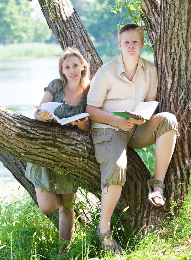 Young Guy And The Girl Prepare For Lessons, Examination In Spring Park Near Lake Stock Photography