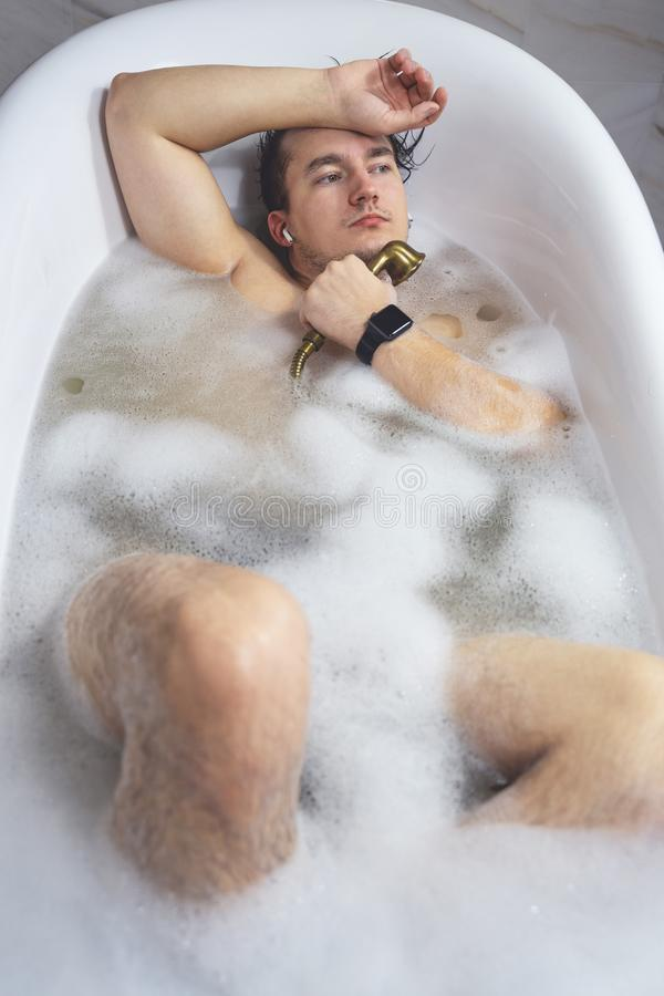 Young guy having a foam bath relaxing. Listening to music in wireless headphones.  royalty free stock image