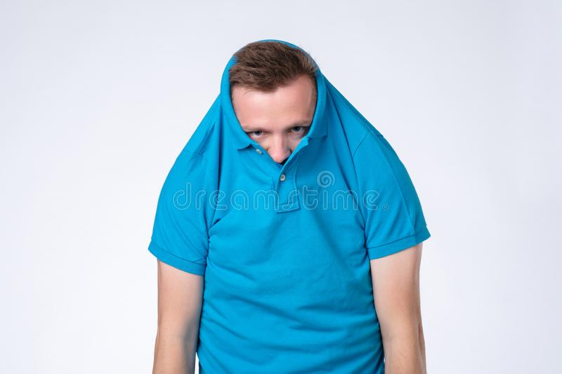 Young guy hiding his face in t-shirt being stressed royalty free stock photos