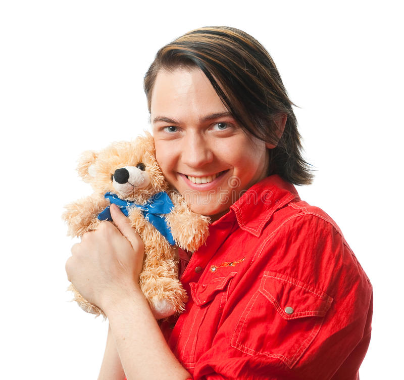 Young guy with his loved toy. Young guy with his loved from childhood toy - teddy bear. Isolated over white in studio stock image