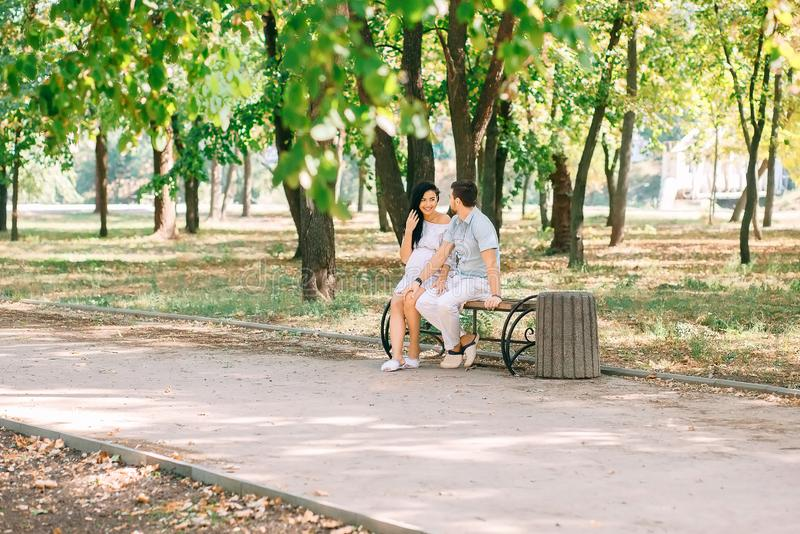 A young guy and his pregnant girl are sitting on a bench, against the background of greenery and trees. In anticipation of a child. First pregnancy I love royalty free stock image