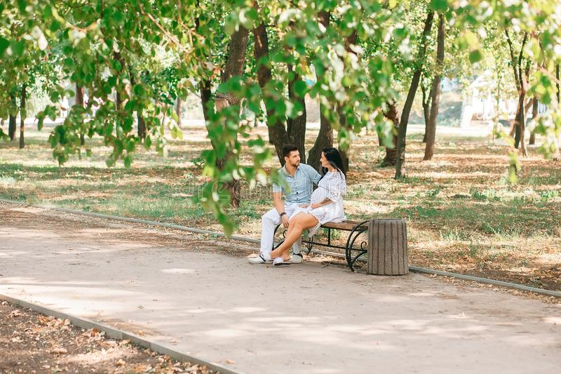 A young guy and his pregnant girl are sitting on a bench, against the background of greenery and trees. In anticipation of a child. First pregnancy I love royalty free stock photo