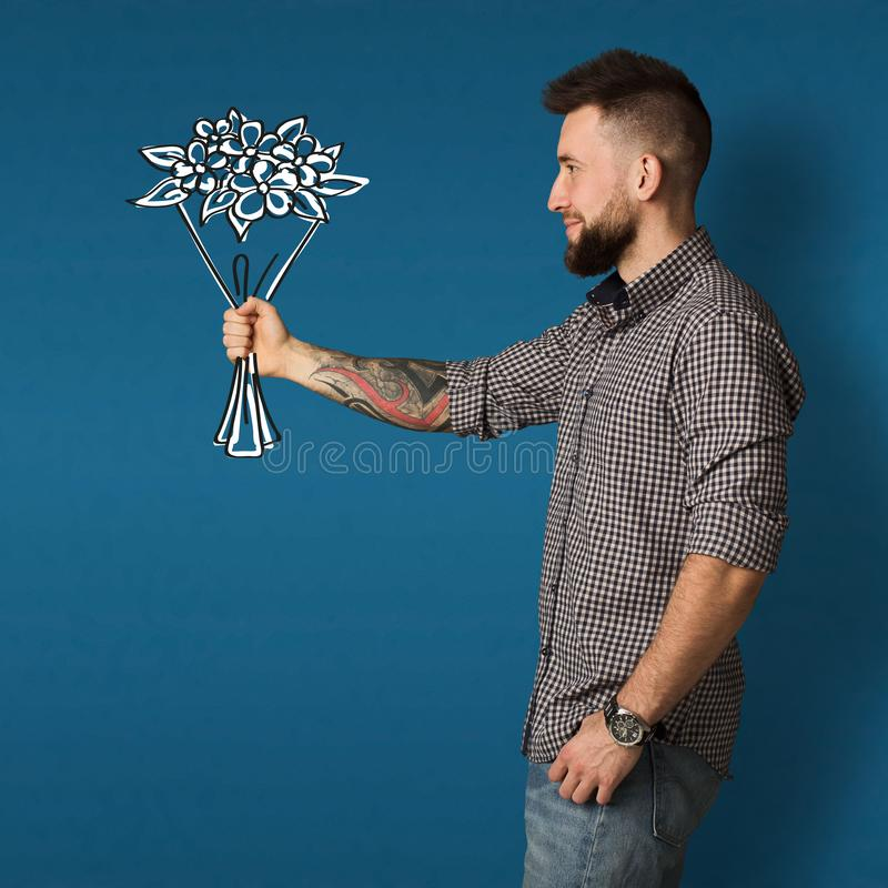 Young guy holding drawn bouquet in hand in studio, collage stock photography