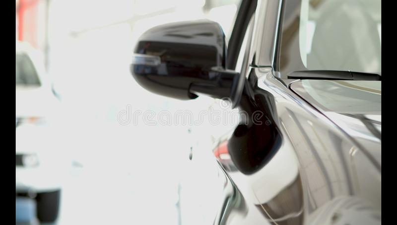 A young guy intently examines a new car in a car dealership royalty free stock images