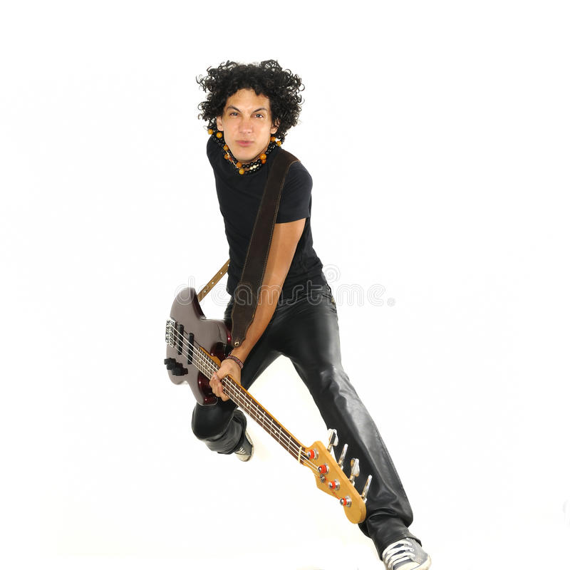 Young guy jumping with electric bass guitar. Portrait of young trendy guy jumping with electric bass guitar isolated on white stock photo