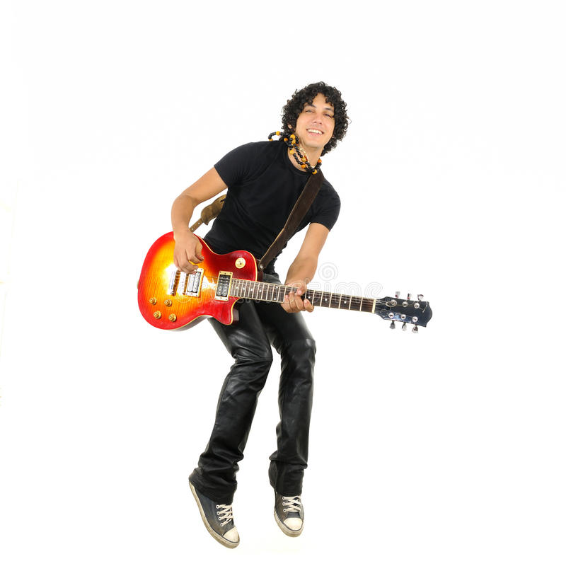 Young guy jumping with electric guitar. Portrait of young trendy guy jumping with electric guitar isolated on white royalty free stock photo