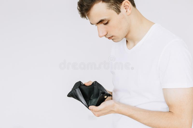 A young guy looks in an empty wallet. Isolated white background.  stock image