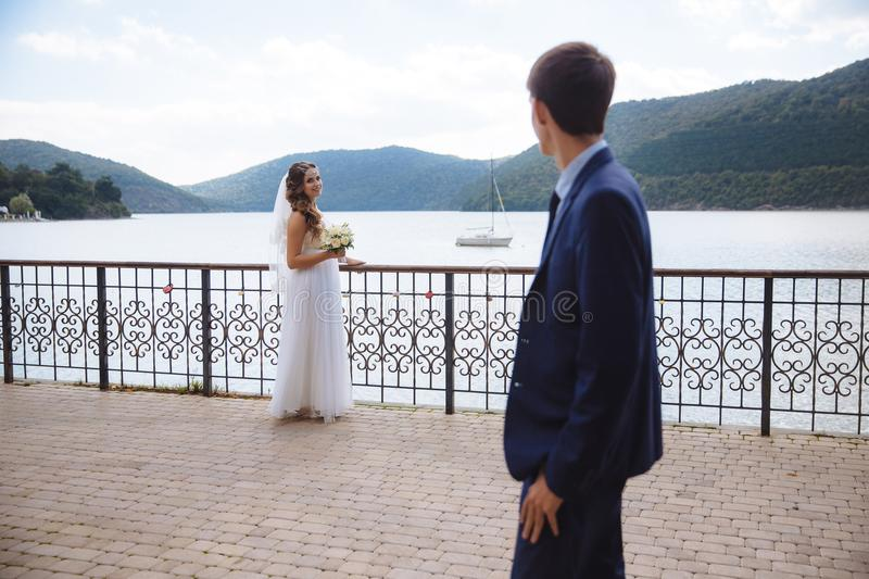 A young guy looks at his bride in a wedding dress against the backdrop of a river along which a boat sails and hills. Covered with green forest. Wedding day in royalty free stock photography