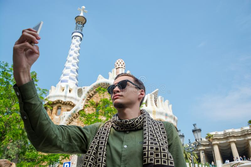 A young guy makes a selfie near a gingerbread house in Güell Pa stock photography