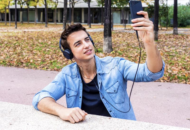 young guy is making selfie on a camera. He is wearing casual trendy wear and big modern headphones stock photos