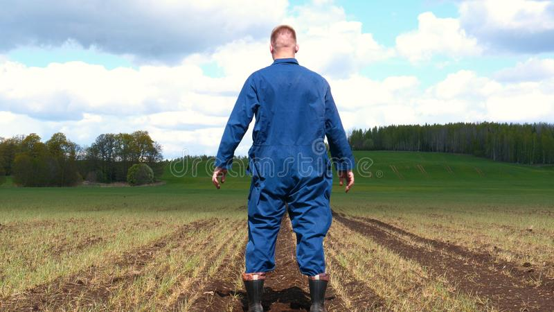 A young guy man, a farmer in a working uniform, walks across a field in rubber boots. Concept of: Freedom, Rubber boots, Lifesty. Le, Farmer, Heaven, Slow stock images