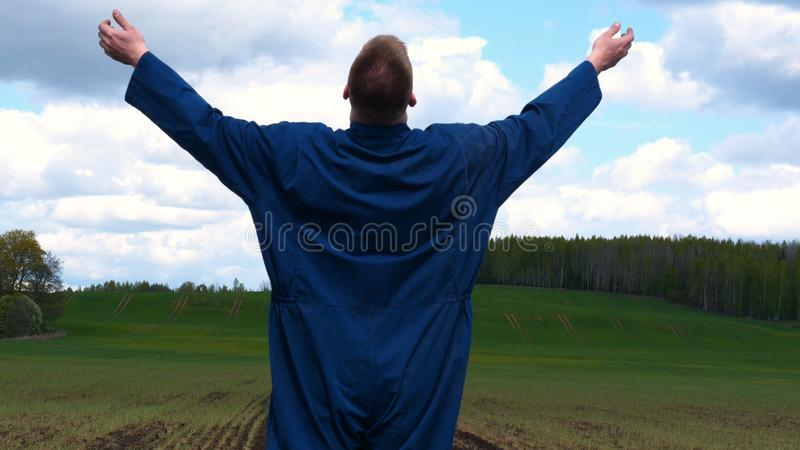 A young guy man, a farmer in a working uniform, walks across a field in rubber boots. Concept of: Freedom, Rubber boots, Lifesty. Le, Farmer, Heaven, Slow royalty free stock photo