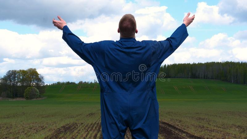 A young guy man, a farmer in a working uniform, walks across a field in rubber boots. Concept of: Freedom, Rubber boots, Lifesty. Le, Farmer, Heaven, Slow stock photos