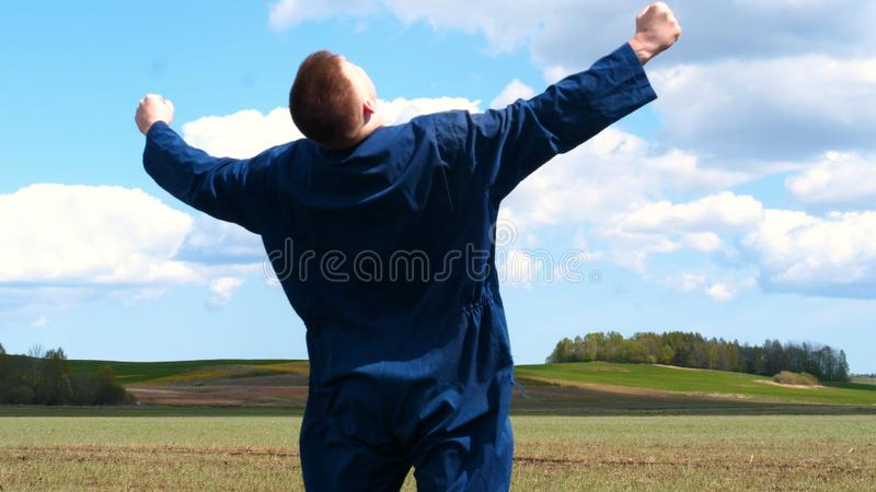 A young guy man, a farmer in a working uniform, walks across a field in rubber boots. Concept of: Freedom, Rubber boots, Lifesty. Le, Farmer, Heaven, Slow royalty free stock image