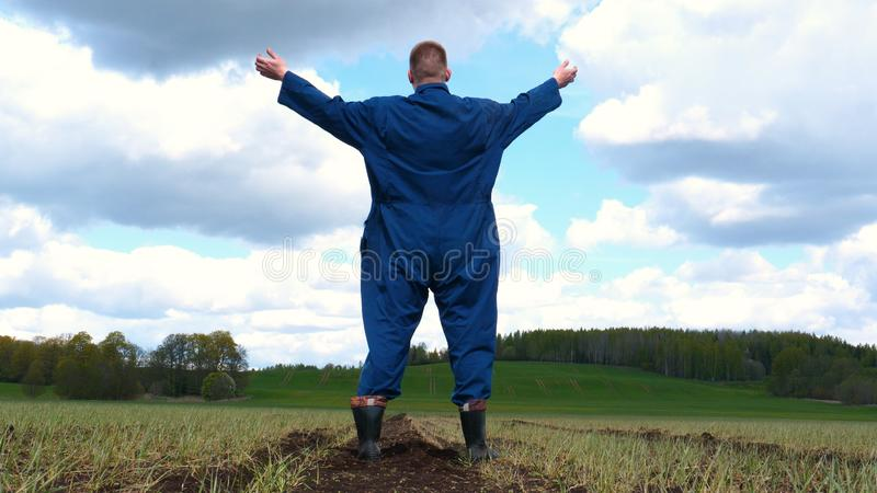 A young guy man, a farmer in a working uniform, walks across a field in rubber boots. Concept of: Freedom, Rubber boots, Lifesty. Le, Farmer, Heaven, Slow stock image