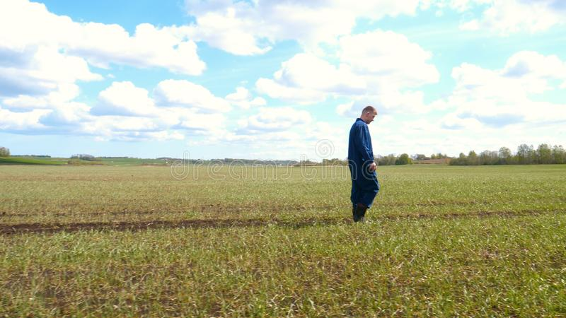 A young guy man, a farmer in a working uniform, walks across a field in rubber boots. Concept of: Freedom, Rubber boots, Lifesty. Le, Farmer, Heaven, Slow royalty free stock photos