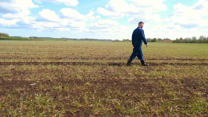 A young guy man, a farmer in a working uniform, walks across a field in rubber boots. Concept of: Freedom, Rubber boots, Lifesty. Le, Farmer, Heaven, Slow stock photography