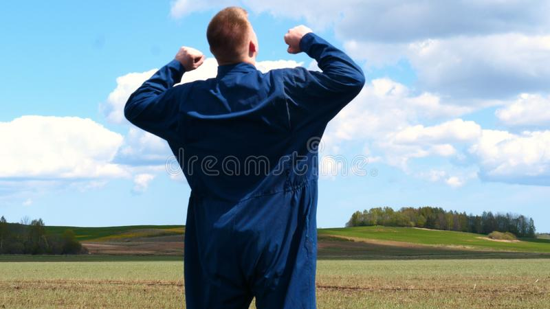 A young guy man, a farmer in a working uniform, walks across a field in rubber boots. Concept of: Freedom, Rubber boots, Lifesty. Le, Farmer, Heaven, Slow royalty free stock images