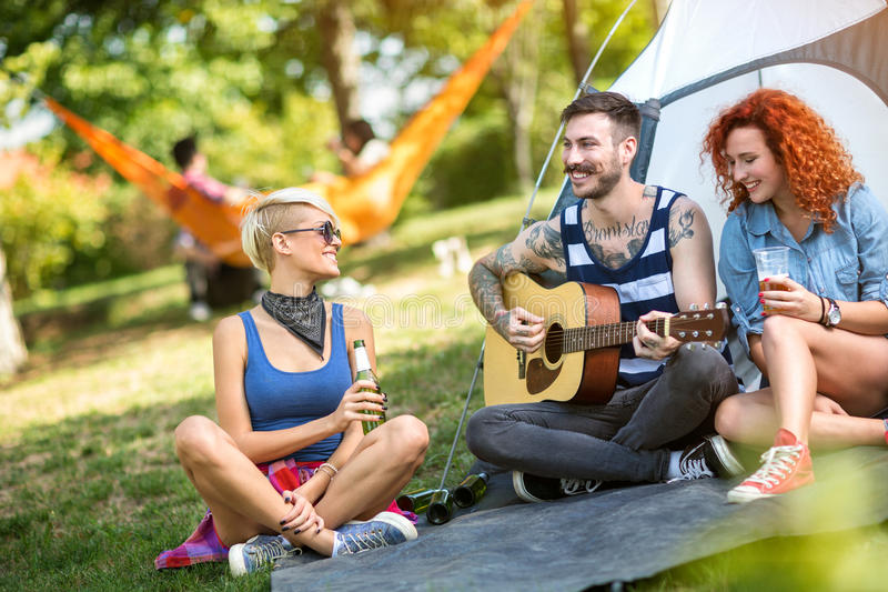 Young guy play guitar while girls enjoy in music and beer. Young tattoo guy play guitar while girls enjoys in music and cold beer at summer camp stock photo