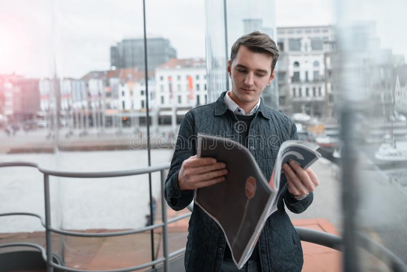 A young guy reads a newspaper inside. royalty free stock photo