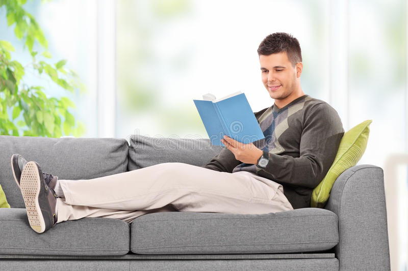 Young guy relaxing with a book at home stock image