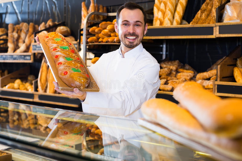 Young guy seller is offering fresh festive cake stock photos
