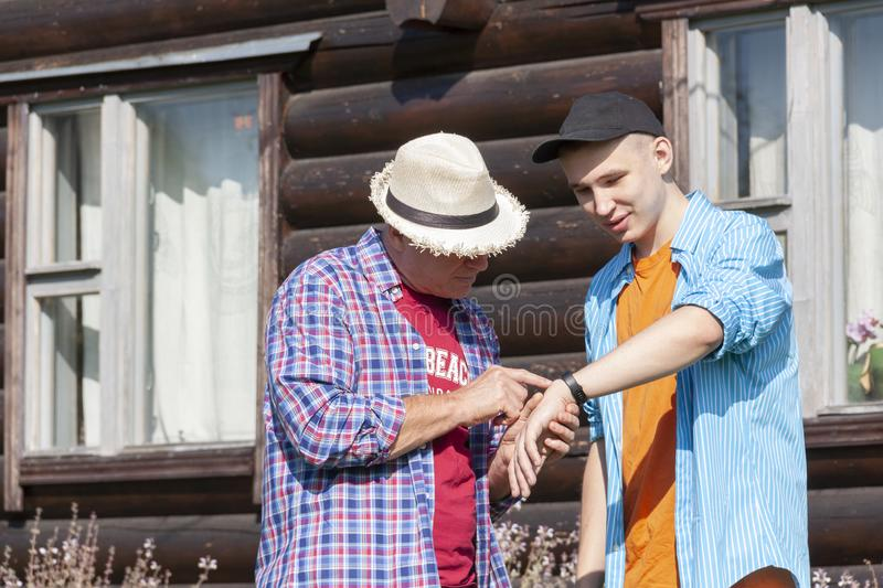 A young guy shows his smartwatch to his father against the background of a log house stock images