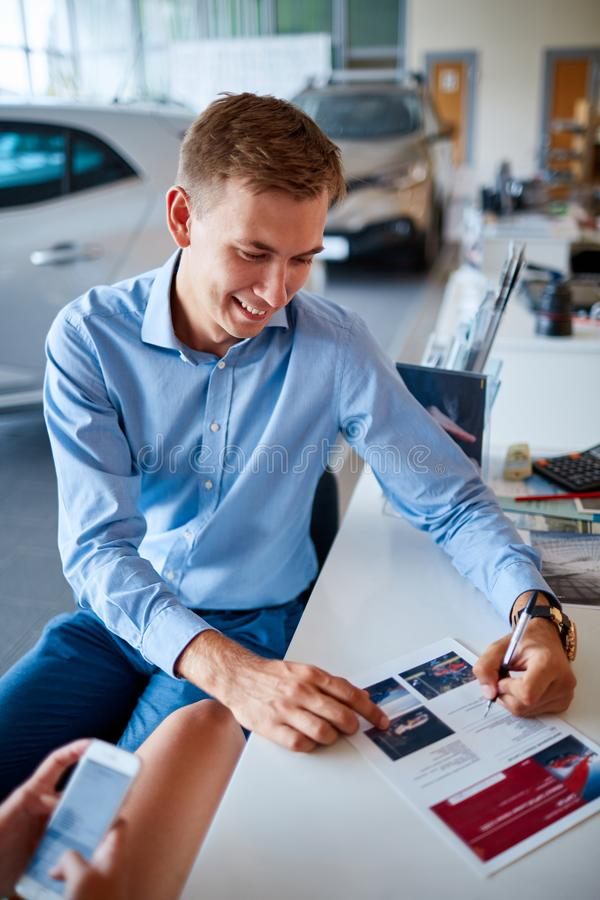 A young guy signing documents in the showroom to buy a new car. royalty free stock image