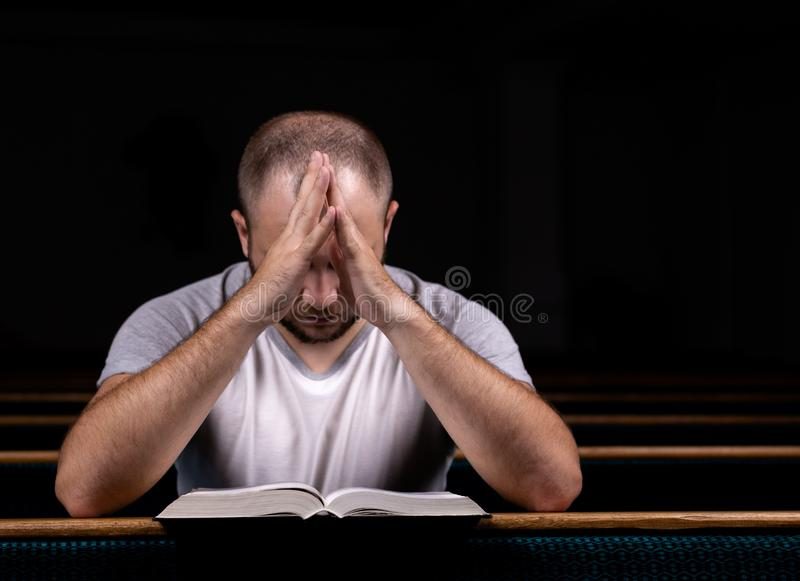 A young guy sits on a church bench, reads the bible and prays. The concept of religion, prayer, faith royalty free stock images