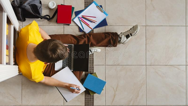 Young guy sitting next to bookshelf at library with laptop. Young male caucasian student sitting next to bookshelf with laptop and making notes on library floor stock image