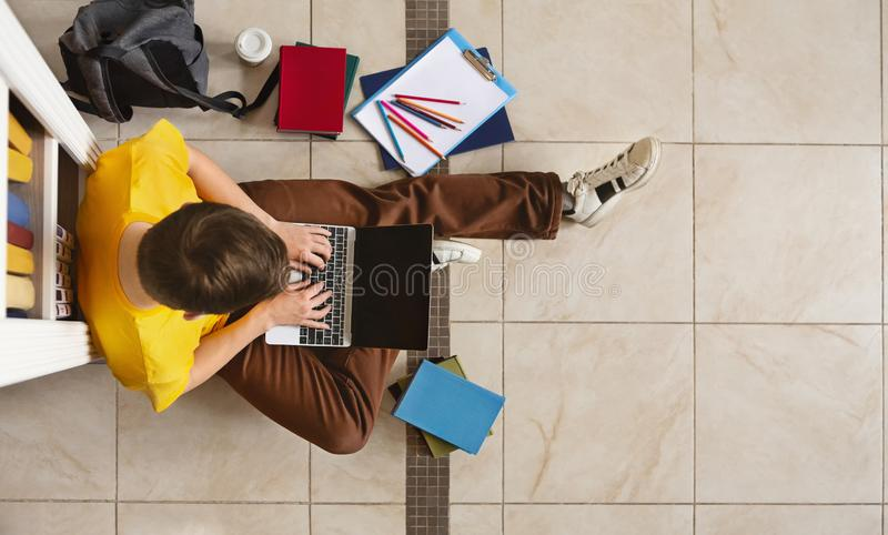 Young guy sitting next to bookshelf at library, using laptop. Young male student sitting next to bookshelf and using laptop on library floor, top view, free royalty free stock photos