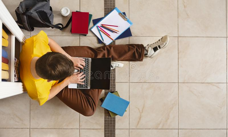 Young guy sitting next to bookshelf at library, using laptop. Young male student sitting next to bookshelf and using laptop on library floor, top view, free royalty free stock photo