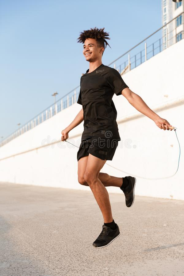 Young guy sportsman jumping with skipping rope outdoors on the beach. Image of handsome young guy sportsman jumping with skipping rope outdoors on the beach royalty free stock image
