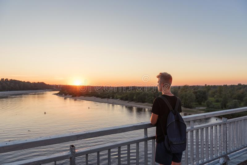 Young guy teenager standing on bridge over river water in lifestyle clothes near steel railing and looking afar at sunset royalty free stock image