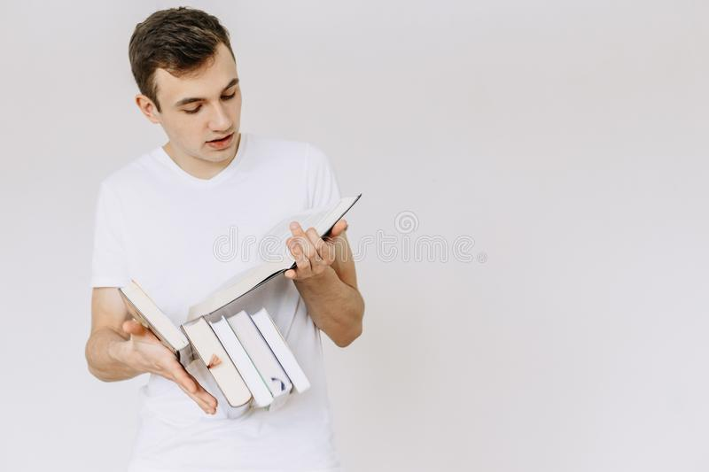 A young guy is standing and reading a book. Books fall from hand. Isolated white background royalty free stock images
