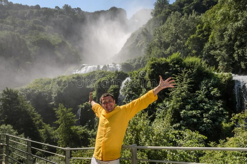 A young guy stands on the background of a waterfall Cascata delle Marmore in Italy royalty free stock photo