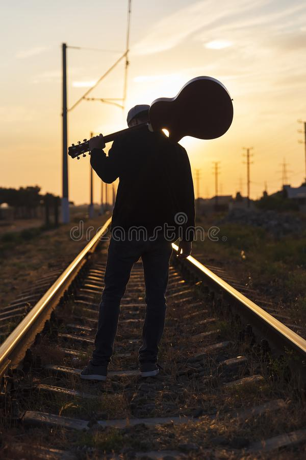 A young guy stands on the rails with a guitar on his shoulders at sunset stock images