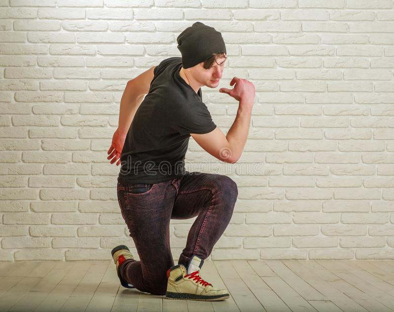Young guy in street clothes style dancing hip-hop and breykdans in studio on brick wall. Young guy in street clothes style dancing hip-hop and breykdans in the royalty free stock photo