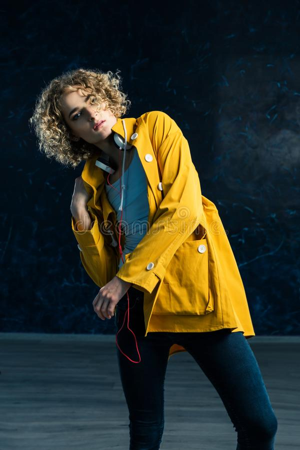 A young guy with a surfer`s hair in a yellow jacket and headphones is dancing against stock images