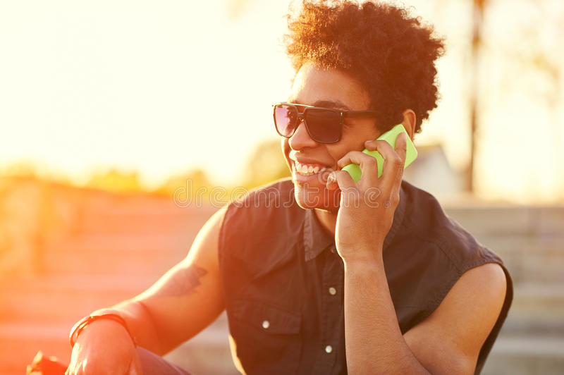 Young guy is talking on phone at sunset background. stock images