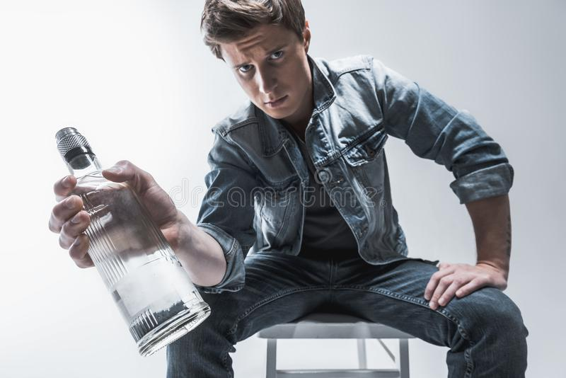 Young guy thinking about alcoholic addiction. Do you really need this. Portrait of pensive man showing bottle of alcohol beverage to camera. He is sitting on stock photography