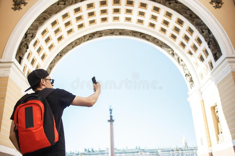 Young guy tourist with backpack taking mobile photo in the palace square in St. Petersburg. Rear view royalty free stock photography