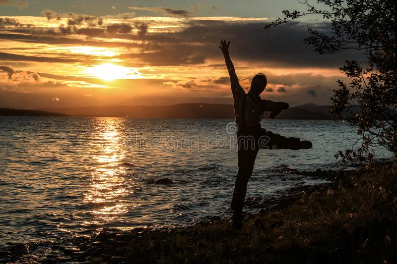 Young guy tourist jumps and enjoys a beautiful sunset over the lake. A midges fly around him, which glows in the rays. Of sunset royalty free stock image