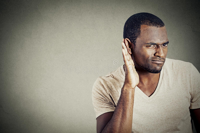 Young guy trying to secretly listen in on a conversation stock photo