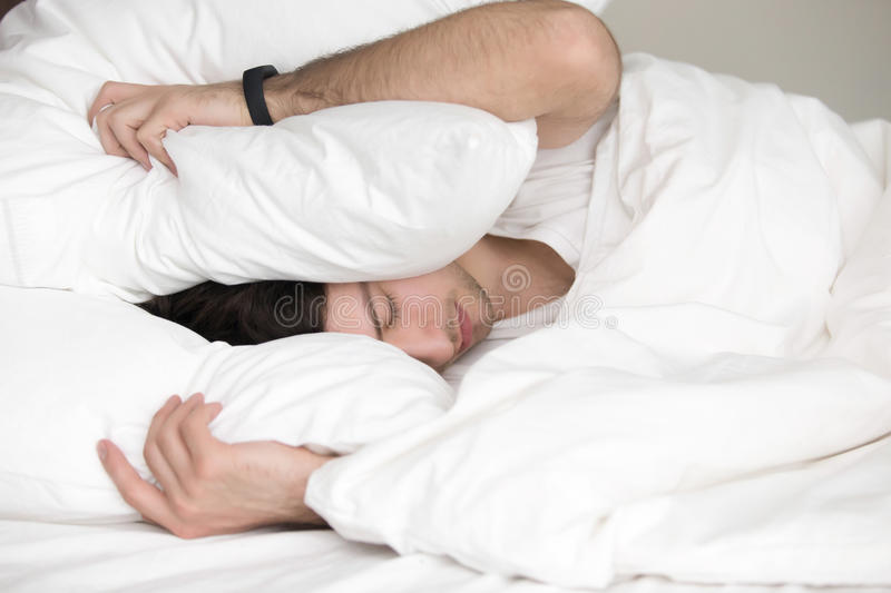 Young guy trying to sleep, covering his head with pillow stock images