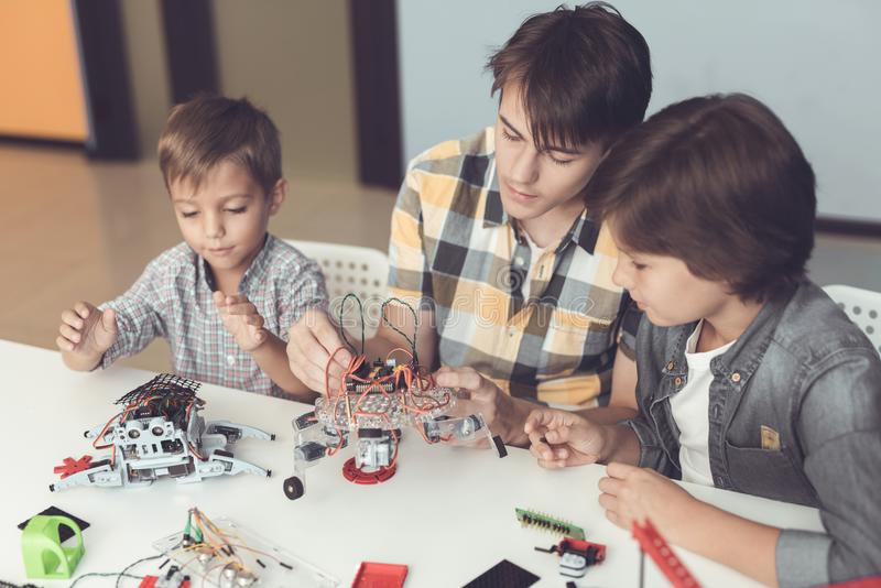 A young guy and two little boys are collecting robots. Around them are parts of different robots and mechanisms stock photo